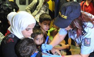 Une policière tchèque en train d'inscrire au marqueur un numéro d'identification sur le bras d'un enfant réfugié syrien.