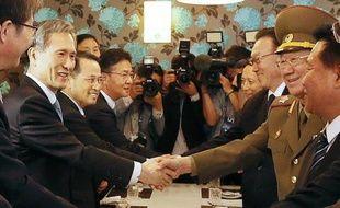Kim Kwan-Jim (g), conseiller à la sécurité de la présidente sud-coréenne Park Geun-HyeSouth, serre la main du vice-président de la Commission nationale de défense nord-coréenne Hwang Pyong-So à Incheon, à l'ouest de Séoul, le 4 octobre 2014
