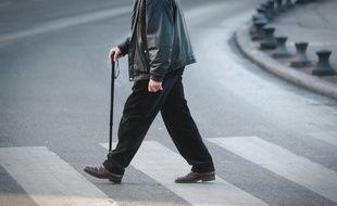 Un homme âgé traverse une route (illustration)