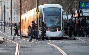 Des piétons traversant devant un tramway à Nantes.