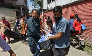 Des Népalais portent un blessé jusqu'à l'hôpital à Katmandou où un nouveau séisme a eu lieu ce mardi 12 mai 2015.