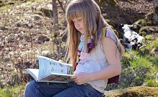 Une petite fille en train de lire.