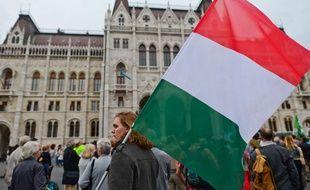 Un manifestant tient un drapeau national hongrois lors de la manifestation devant le Parlement hongrois, le jour du référendum de quotas de migrants hongrois. Le dimanche 2 Octobre 2016, à Budapest, Hongrie.