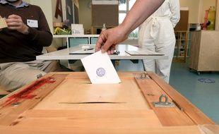 Un électeur dépose son bulletin dans une urne à Espoo en Finlande, le 13 juin 2021.