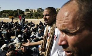 Des migrants tunisens rassemblés dans un stade de foot sur l'île italienne de Lampedusa, le 13 février 2011.