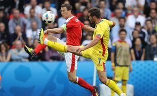 Le Suisse Stephan Lichtsteiner (à gauche), à la lutte avec le Roumain Alexandru Chipciu, lors de l'Euro 2016, le 15 juin 2016.