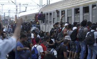 Des migrants tentent d'embarquer à bord d'un train à destination de la Serbie, dans la gare Gevgelija, dans le sud de la Macédoine, le 12 août 2015.