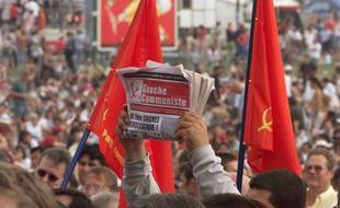 un participant brandit un exemplaire de la Gauche communiste à la Fête de l'Huma, le 12 septembre 1999, à La Courneuve (Seine-Saint-Denis).