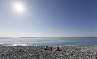 Des vacanciers profitent de la chaleur sur une plage de Nice le 7 mars 2014