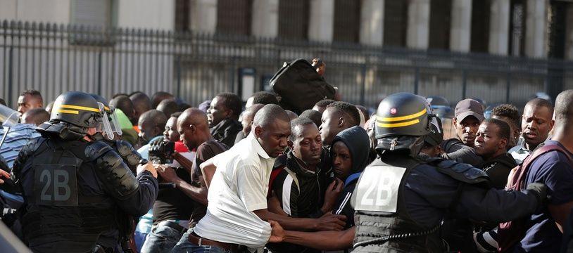 """Des CRS repoussent les """"gilets noirs"""" aux abords du panthéon, vendredi 12 juillet."""