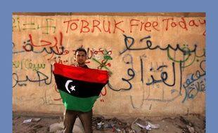 Un manifestant anti-Kadhafi brandit le drapeau de l'ancienne monarchie libyenne d'Idris Ier, le 24 février 2011 à Tobrouk.