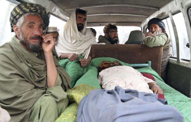 Des civils afghans près du corps d'une des victimes, le 11 mars 2012