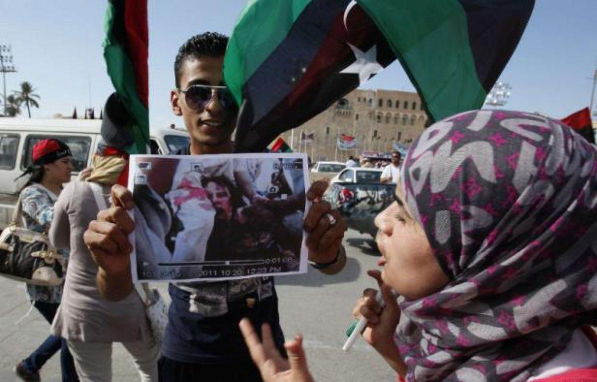 Un Libyen tient une photo de la dépouille de Kadhafi, le 20 octobre 2011. – A.M AL-FERGANY/AP/SIPA