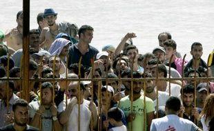 Des migrants attendent derrière une barrière pour entrer dans le stade de l'ïle de Koos pour se faire enregistrer administrativement, le 12 août 2015