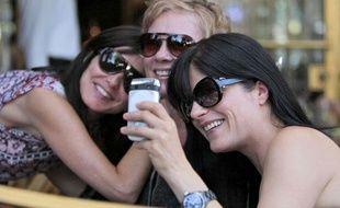 """Des jeunes femmes font un """"selfie"""", une photo de groupe prise soi-même."""