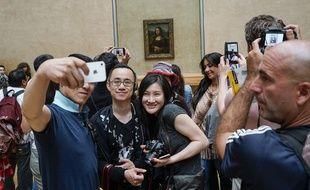 Des visiteurs du musée du Louvre font un selfie devant