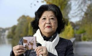 Cambodian Billon Ung Boun Hor, widow of former Cambodian National Assembly President who disappeared in 1975 during the Khmer Rouge takeover of Cambodia, holds a picture of them on Novembre 13, 2014 in Nogent-sur-Marne, eastern Paris. Billon Ung Boun Hor filed a complaint against France in 1999 for the disappearance of her husband Ung Boun Hor, Cambodian National Assembly President who, like hundreds of people, took refuge at the French embassy in Phnom Penh after the Khmers Rouges ordered the evacuation of the Cambodian capital on April 17, 1975. Public prosecutor of Paris asked on November 13, 2014 the case to be dismissed. AFP PHOTO BERTRAND GUAY