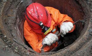 Un ouvrier travaillant dans un égout (illustration).
