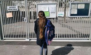Une écolière devant une école fermée (illustration)