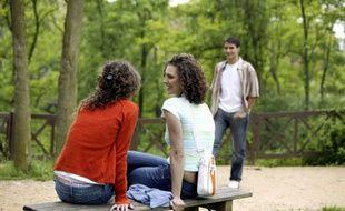 Un jeune homme se dirige vers deux femmes assises sur un banc