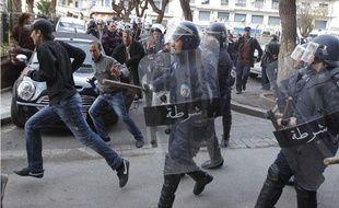 Des policiers algériens courent après des manifestants, samedi 19 février à Alger