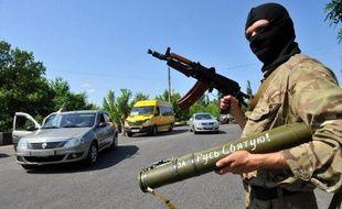 Un militant prorusse surveille les voitures le 20 mai 2014 à un point de passage près de la ville de Kramatorsk, dans l'est du pays