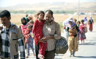 Un Irakien de la communauté yézidie traverse la frontière entre l'Irak et la Syrie à Fishkhabur le 11 août 2014