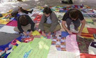 """Des membres de l'association de solidarité Unis-Cité réalisent un patchwork composé de morceaux de tissus collectés partout en France, le 7 juin 2002 à Paris, dans le cadre de l'opération """"le Patchwork des différences"""""""