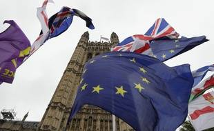 A confusion of various flags fly outside Parliament in London, Monday, Oct. 21, 2019.  The European Commission says the fact that British Prime Minister Boris Johnson did not sign a letter requesting a three-month extension of the Brexit deadline has no impact on whether it is valid and that the European Union is considering the request.