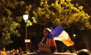 Une femme célèbre la victoire des Bleus sur les Champs-Elysées
