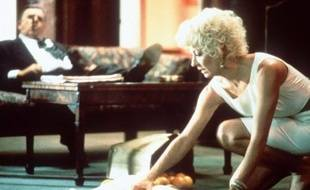 """Au deuxième plan, Pat Hingle regarde Angelica Huston dans le film """"Les Arnaqueurs"""""""