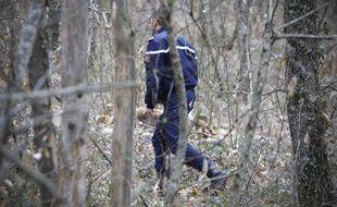 Un gendarme menant des recherches dans un bois. Illustration