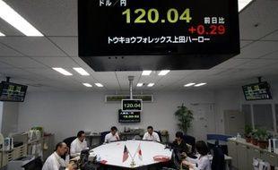 Des traders sous un tableau des taux de change, le 5 décembre 2014 à Tokyo