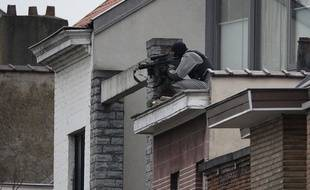 Un membre des forces spéciales prend position près de la maison perquisitionnée.