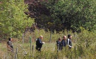 Berkane Makhlouf (d), le père de Fiona, une fillette de 5 ans, escorté par des officiers de police le 13 mai 2014 à Aydat, lors de la reprise des fouilles un an après sa disparition