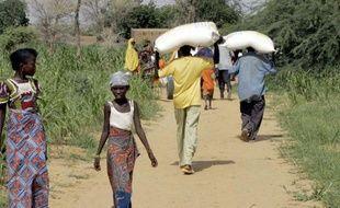 Des hommes portent des sacs de nourriture à Tolkobeye au Niger le 8 août 2005