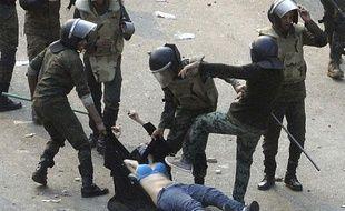 Des soldats égyptiens arrêtent une manifestante lors d'affrontement place Tahrir, au Caire, le 17 décembre 2011.