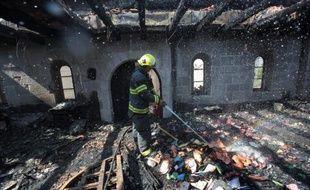 Un pompier éteint le 18 juin 2015 les derniers foyers de l'incendie ayant ravagé le sanctuaire chrétien de Tabgha en Israël, sur les rives du lac de Tibériade