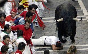 Un homme tombé près d'un taureau, lors d'un «encierro» de San Fermin, le 9 juillet 2003 à Pampelune.