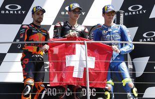 De gauche à droite, Miguel Oliveira, Fabio Quartararo, et Joan Mir avec le drapeau suisse pour honorer le pilote suisse de 19 ans Jason Dupasquier, lors de la cérémonie de podium à l'issue du Grand Prix Motogp d'Italie sur le circuit du Mugello, à Scarperia, en Italie, dimanche 30 mai 2021.