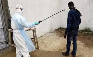 Un visiteur est décontaminé à son arrivée à l'hôpital Island à Monrovia (Libéria) où il est venu apporter de la nourriture à des proches souffrant du virus Ebola, le 26 septembre 2014