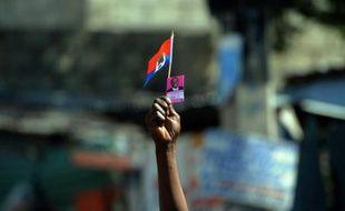 Un sympathisant du président au pouvoir, Jovenel Moïse, tient un drapeau haïtien