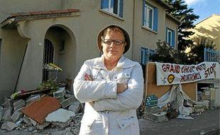 Marie-France Ragoso, du comité de quartier, devant un mur démoli.