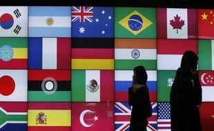 Des personnes devant un panneaux montrant les drapaux des pays du monde entier, lors du G20 de Séoul, le 5 novembre 2010.