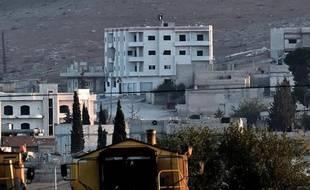 Un drapeau noir du groupe Etat Islamique flotte sur le toit d'un immeuble de la ville de Kobané, le 6 octobre 2014 en Syrie