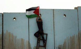 Un jeune Palestinien escalade le mur qui sépare Israël de la Palestine, près de Ramallah le 15 mai 2008