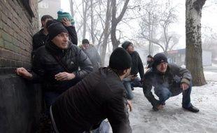Des passants se mettent à l'abri pendant le bombardement d'un quartier de la ville de Donetsk, dans l'est séparatiste de l'Ukraine, le 30 janvier 2015