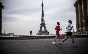 Paris, le 17 mars 2020. Deux hommes font leur footing non loin de la Tour Eiffel alors que le confinement a été ordonné en raison de l'épidémie de coronavirus.