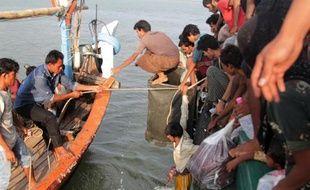 Des pêcheurs de la province d'Aceh en Indonésie (g) aident des migrants Rohingya à accoster près de la ville de Geulumpang, le 20 mai 2015