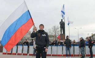 Un homme tient un drapeau nationaliste sur une place de Simferopol en Crimée, région autonome d'Ukraine.